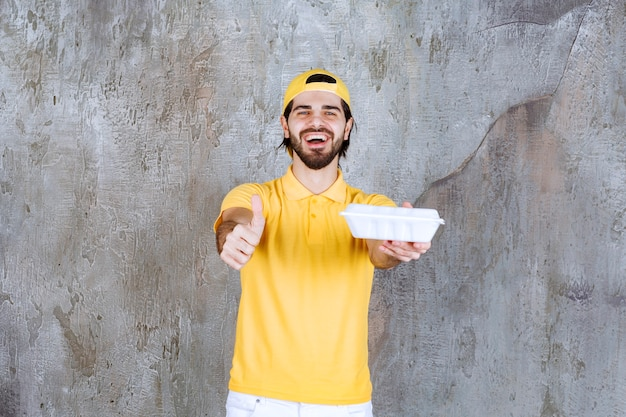 Courier in yellow uniform delivering a plastic takeaway box and showing positive hand sign.