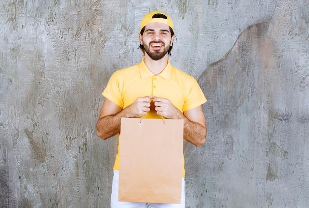 Corriere in uniforme gialla che tiene una borsa della spesa di cartone.
