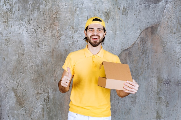 Courier in yellow uniform holding an open cardboard box and enjoying the product