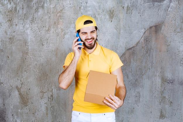 Corriere in uniforme gialla che tiene una scatola di cartone aperta e prende ordini via telefono