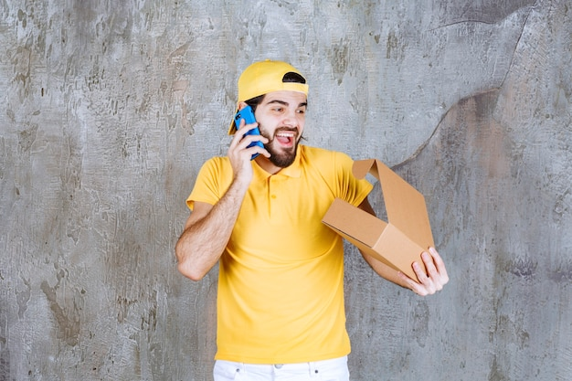 Courier in yellow uniform holding an open cardboard box and taking orders via phone.