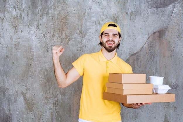 Corriere in uniforme gialla che tiene pacchi da asporto e scatole di cartone e mostra un segno positivo