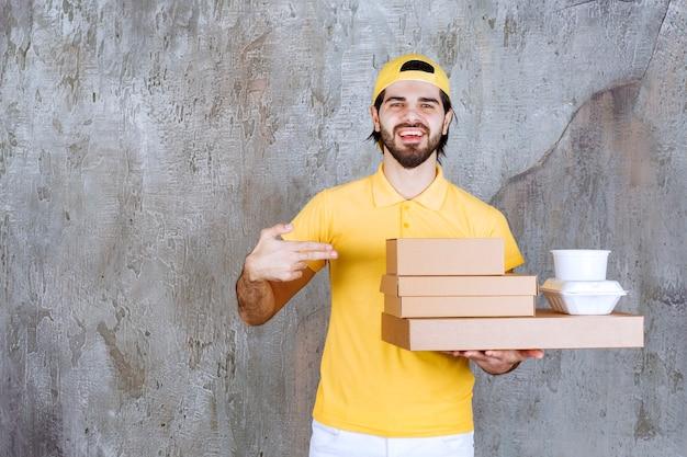 Corriere in uniforme gialla con pacchi da asporto e scatole di cartone.