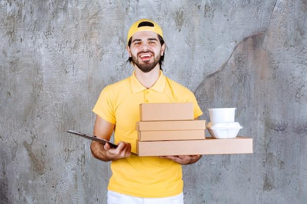 Corriere in uniforme gialla che tiene pacchi da asporto e borsa della spesa e controlla l'elenco dei clienti.