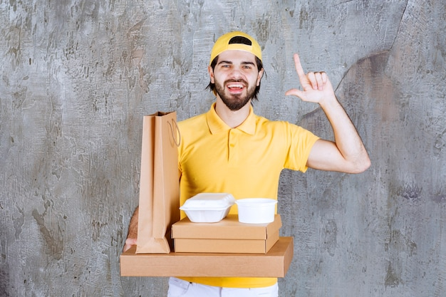 Courier in yellow uniform holding takeaway parcels and shopping bag and looks confused or thinking