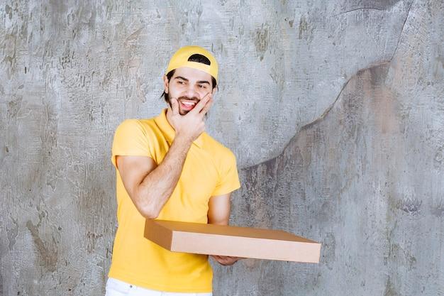 Corriere in uniforme gialla che tiene in mano una scatola di pizza da asporto e sembra confuso e pensieroso.