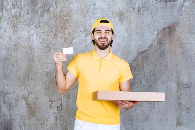 Corriere in uniforme gialla che tiene una scatola di pizza da asporto e presenta il suo biglietto da visita.