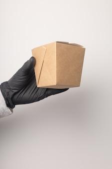 手袋をはめた宅配便は配達箱を持っています