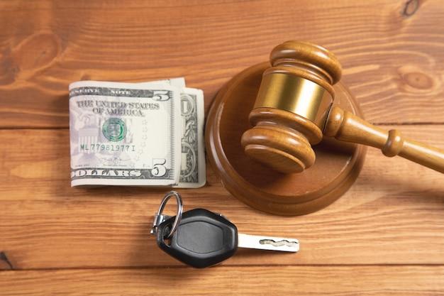 Судебный молоток с деньгами и ключами от машины на столе