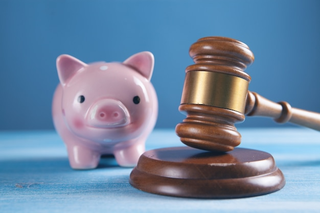 Court gavel with a piggy bank on the table