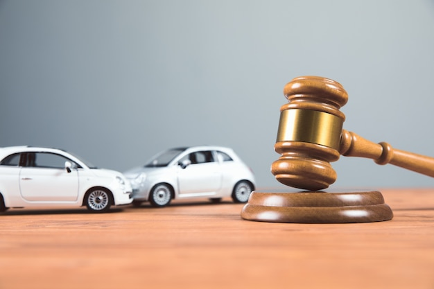 Court gavel with toy cars on the table accident