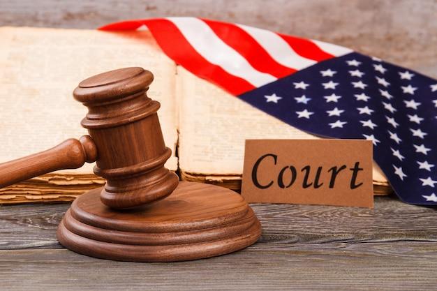 アメリカ合衆国の裁判所。木製の裁判官ガベルは、木製の机の上の私たちの旗と一緒に。