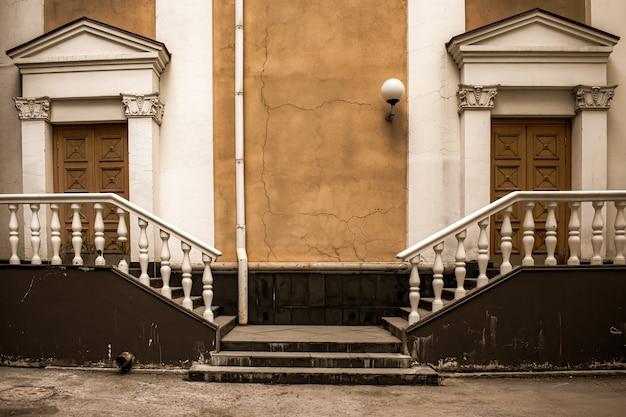 Двор старинного архитектурного сооружения, две массивные двери с белокаменными лестницами по бокам.
