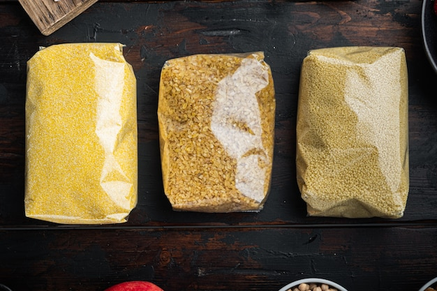Couscous, bulgur and polenta in pounch, top view on dark wooden table.