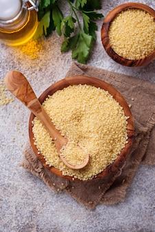Couscous grain in wooden bowl