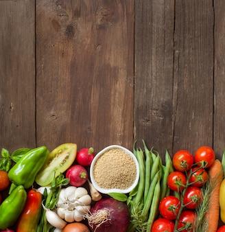 Кускус в миске и свежие овощи на деревянном столе с копией пространства