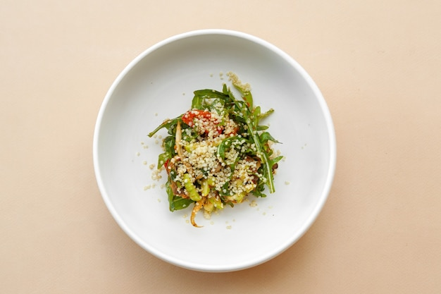 Couscous salad, tomatoes and rucola, beige table, top view