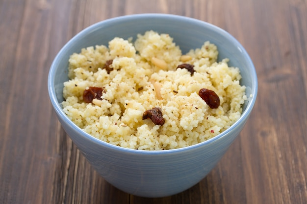 Couscous with dry fruits on blue bowl on wooden table