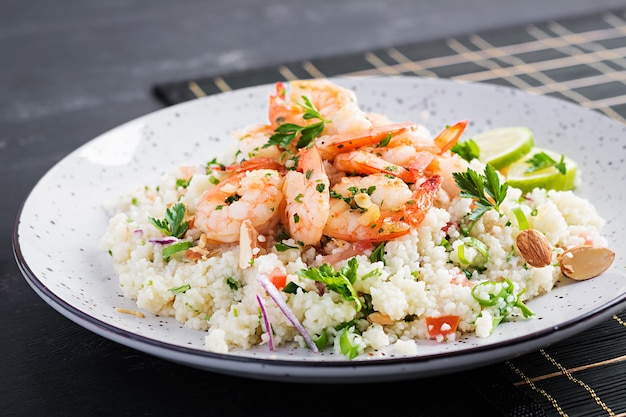 Couscous with roasted shrimps, tomatoes, red onions, almond nuts and parsley. moroccan food with couscous and prawns.