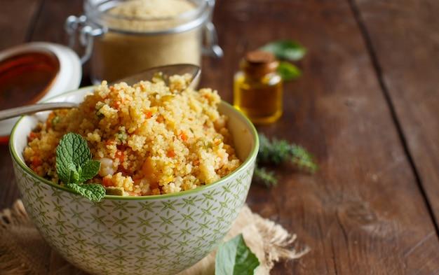 Кускус с креветками и овощами в миске крупным планом