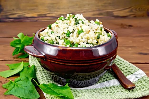 나무 판자 배경에 냅킨, 바질과 숟가락에 점토 그릇에 시금치와 녹색 완두콩 쿠스쿠스