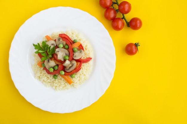 Кускус с овощами в белой тарелке. вид сверху. скопируйте пространство. крупный план.
