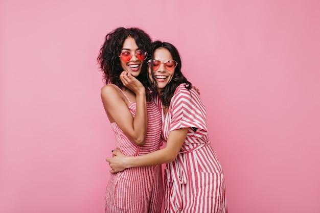 Cugini in capelli ricci scuri di ottimo umore in posa per il ritratto. le ragazze in abiti rosa si divertono.