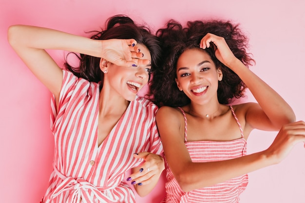 멋진 분위기의 사촌들이 기분 좋게 바닥에 누워 있습니다. 소녀는 클로즈 업 초상화를 위해 분홍색 옷을 입고 진지한 미소로 포즈를 취합니다.
