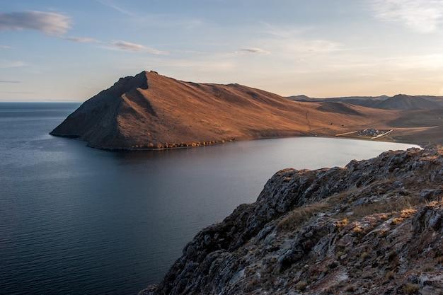 日没時の家と岩の入り江