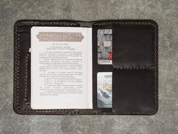 Обложка для документов с двумя картами и паспортом рф лежит на серой фактурной поверхности.