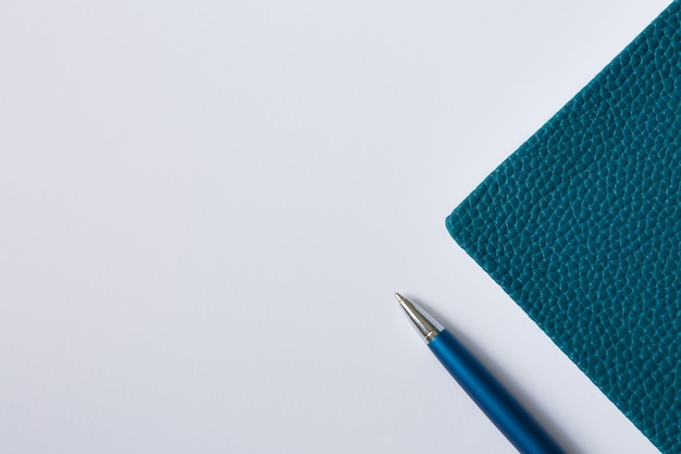 Cover of green notebook, diary or book on white paper and blue metal pen flat lay