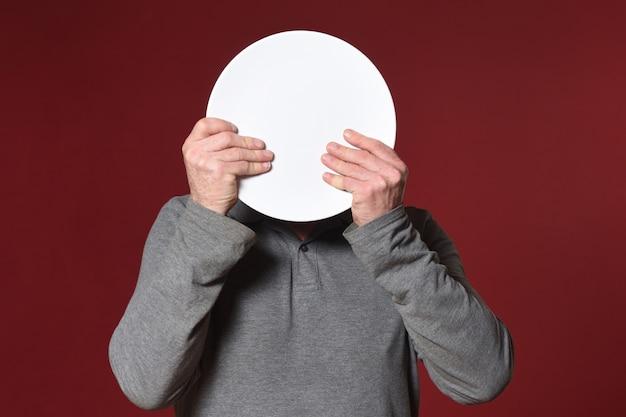 赤い背景の上の皿で顔を覆う