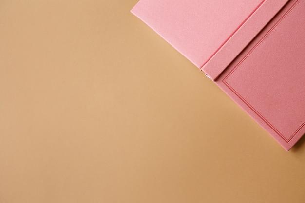 ピンクのノート、日記、または茶色の紙の本の表紙フラットレイ