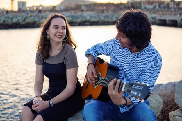커버밴드 음악가 커플은 어쿠스틱 기타를 연주하고 해변 근처에서 노래를 부릅니다. 배경에 바다