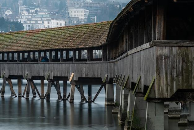 スイスのルツェルンの建物に囲まれたルツェルンイエズス会教会近くの屋根付き橋