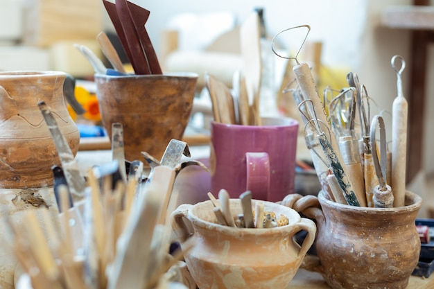 Covered in clay. pottery tools for carving and creating new figures being collected in old clay pots
