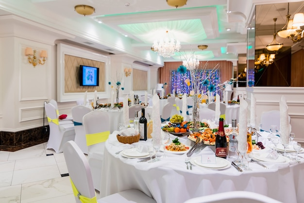 Covered dining table in bright white luxury banquet hall for wedding events