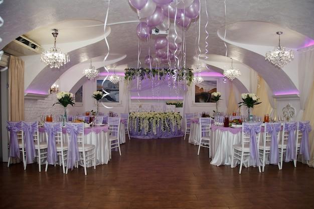 テーブルと花飾りのある結婚披露宴用の屋根付きホール。新婚夫婦とゲストのためのお祝いレストラン。素晴らしいデザインのインテリア。イベントのための豪華なデザイン。サイトの著作権スペース