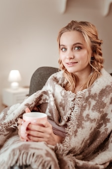 毛布で覆われています。居心地の良い肘掛け椅子に座っている大きな青い目と完璧な輝く肌を持つ魅力的な長髪の女性