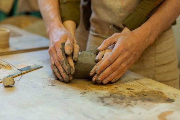 粘土で覆われています。粘土を優しく抱きしめながら陶芸工房でマスタークラスを持っているロマンチックな素敵なカップル