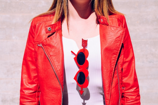Covered neckline of woman with funny red cheeky glasses with cupid arrow.