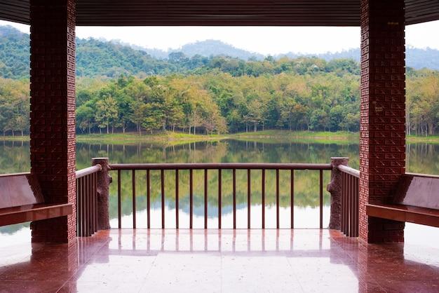 レンガの石の柱で覆われたテラス、晴れた夏の日に緑の木々と川に囲まれたフェンスで囲まれたタイル張りの床