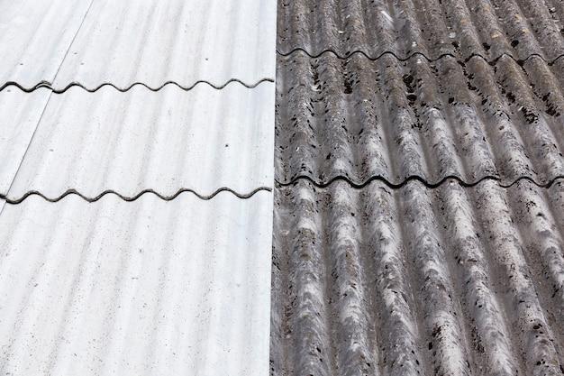 Крыша покрыта шифером, часть которого из старого шифера, потемневшего и грязного, а вторая половина - из нового материала, крупным планом.