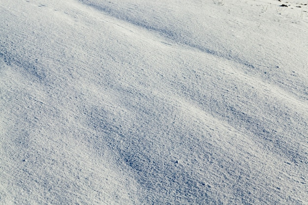 Covered with white snow drifts surface. photo closeup. on snow formed irregularities. photo close-up, small depth of field