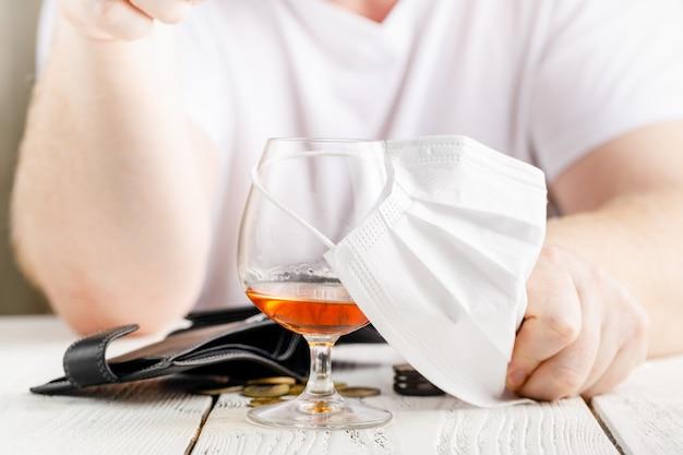 Покрытие стакана спирта медицинской маски для лица. концепция отмененных социальных мероприятий во время пандемического и коронирусного вируса