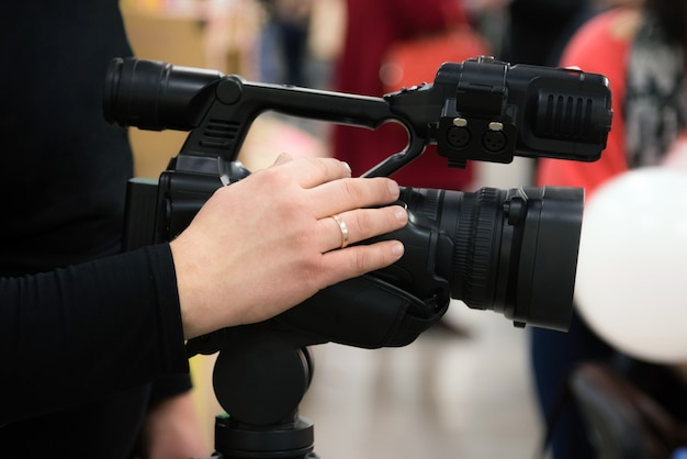 Covering an event with a video camera. videographer films with video camera.
