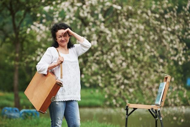 햇빛으로부터 손으로 눈을 가리기. 악기 케이스를 든 성숙한 화가가 아름다운 봄 공원에서 산책