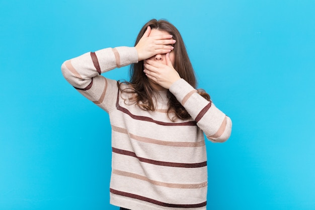 Covering face with both hands saying no! refusing pictures or forbidding photos