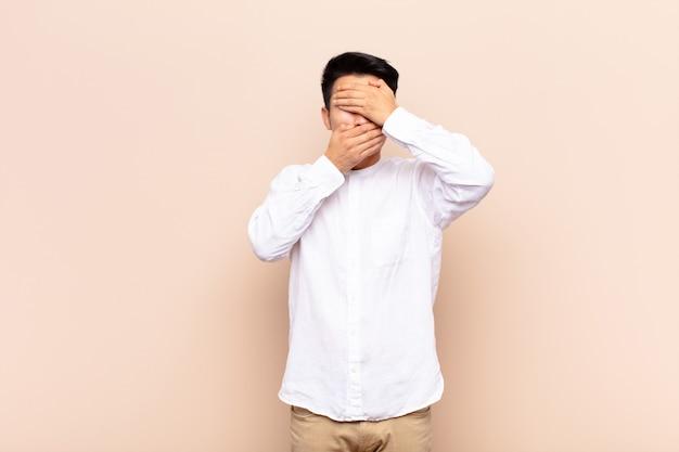 Закрывая лицо обеими руками, говоря «нет» камере! отказ от фотографий или запрещение фотографий