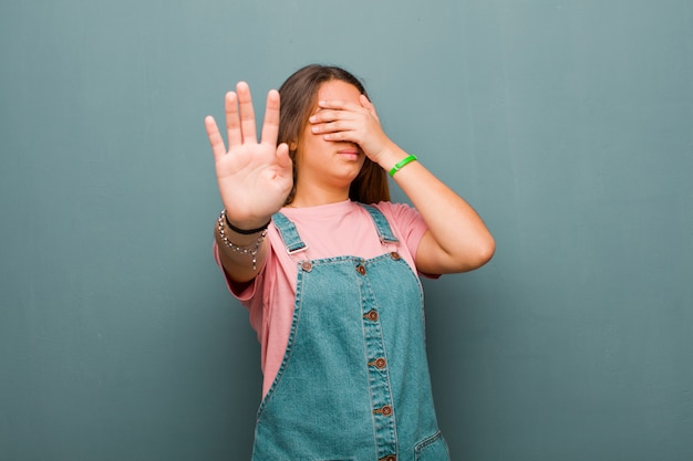 Закрыв лицо рукой и положив другую руку вперед, отказываясь от фотографий или картинок
